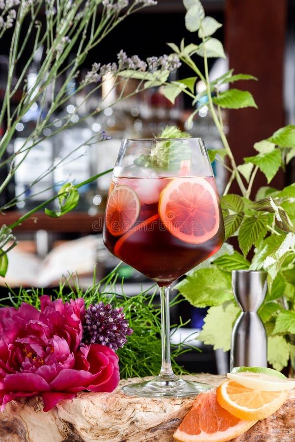 与冰、石灰和薄菏的刷新的红色夏天鸡尾酒在鲜花背景的美丽的玻璃  免版税库存照片