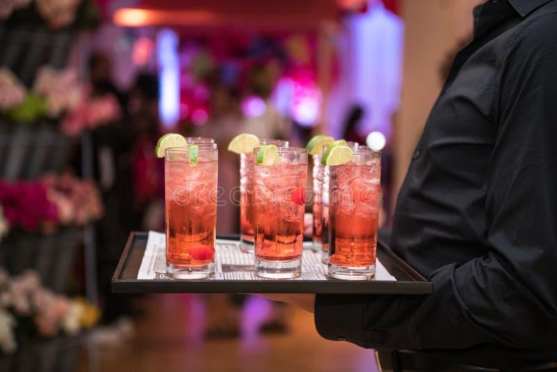 与冰和柠檬的刷新的酒精红色鸡尾酒在平衡事件党的侍者板材 库存照片