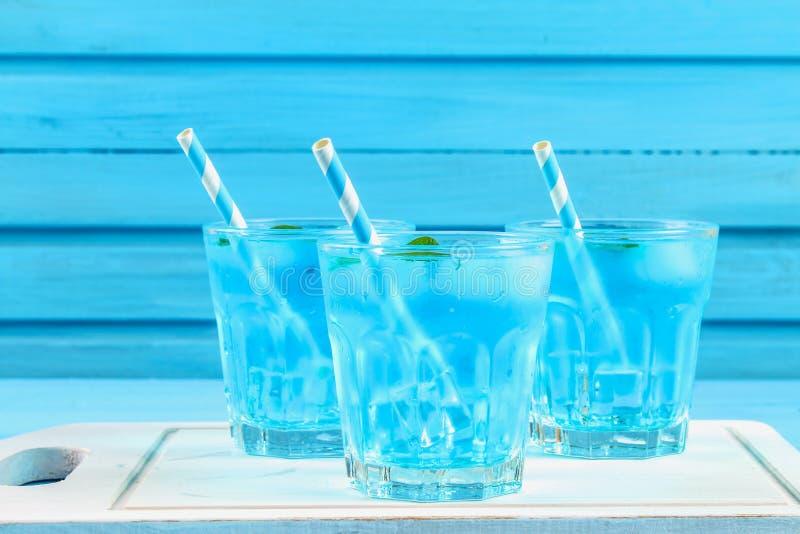 与冰和薄菏的蓝色鸡尾酒在一个白色木板的玻璃在一张蓝色桌上 库存图片