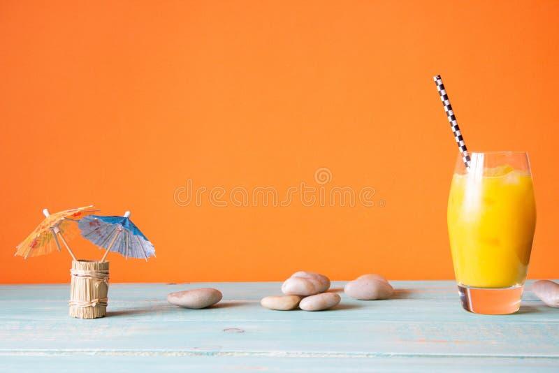与冰和鸡尾酒伞的橙汁过去 橙色背景 背景概念框架沙子贝壳夏天 免版税库存照片