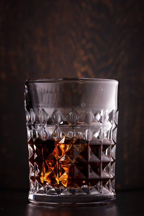 与冰在玻璃,土气木背景的威士忌酒 免版税库存图片