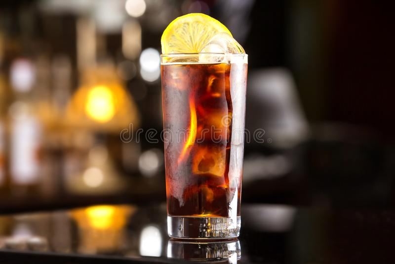 与冰块和柠檬的兰姆酒可乐偶然鸡尾酒在欢乐酒吧 库存照片