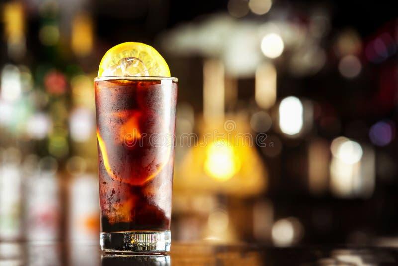 与冰块和柠檬的兰姆酒可乐偶然鸡尾酒在欢乐酒吧 免版税库存照片