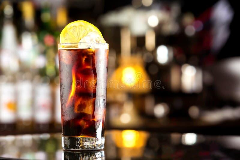 与冰块和柠檬的兰姆酒可乐偶然鸡尾酒在欢乐酒吧 图库摄影