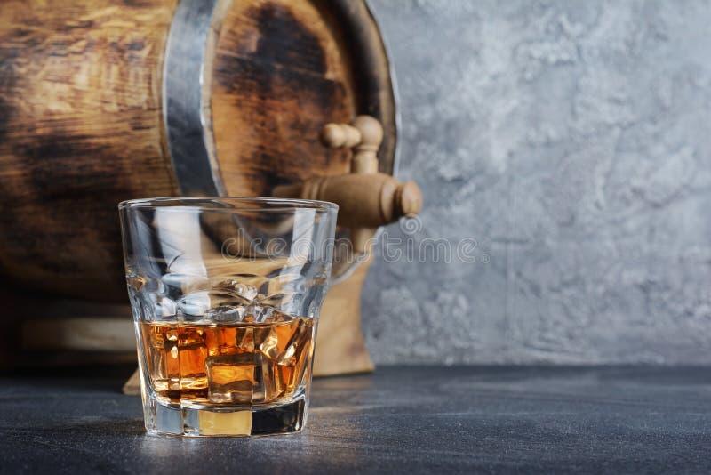 与冰块在老时尚玻璃和葡萄酒木桶的强的酒精饮料苏格兰威士忌酒在地窖里 免版税库存照片