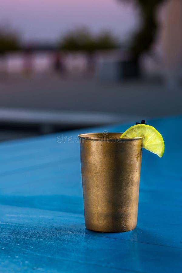 与冰块的兰姆酒可乐偶然在夏天酒吧的鸡尾酒和石灰站立背景 库存照片
