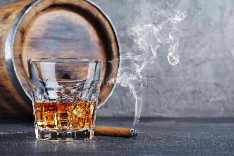 与冰块的强的酒精饮料苏格兰威士忌酒在与抽烟的雪茄和葡萄酒木桶的老时尚玻璃在地窖里 免版税库存图片