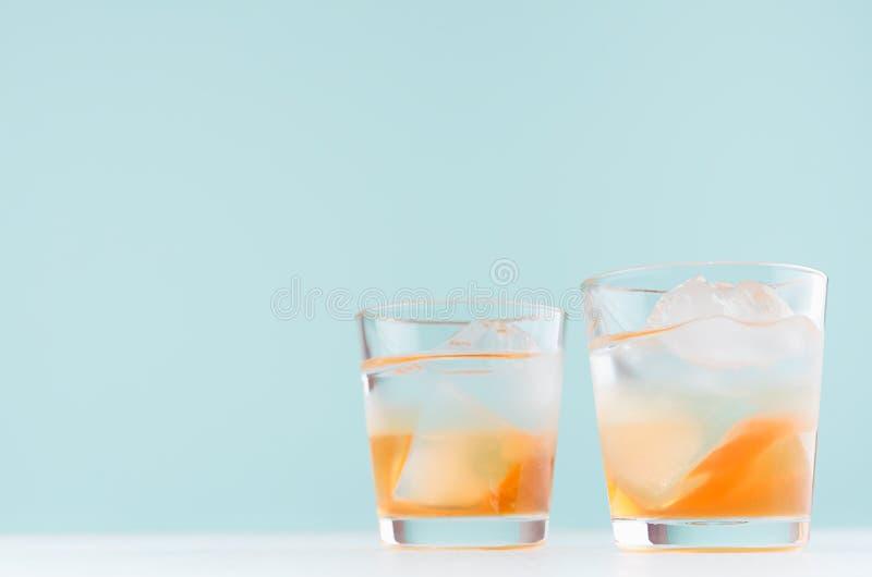 与冰块的热带新鲜的层状鸡尾酒,在misted小玻璃的桔子酒在淡色蓝色背景 免版税图库摄影