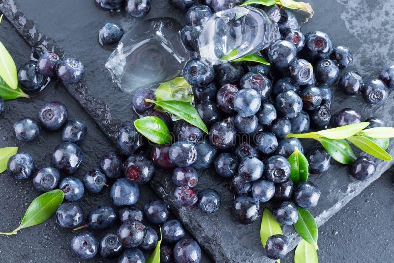 与冰块的蓝莓在板岩板材 免版税库存照片