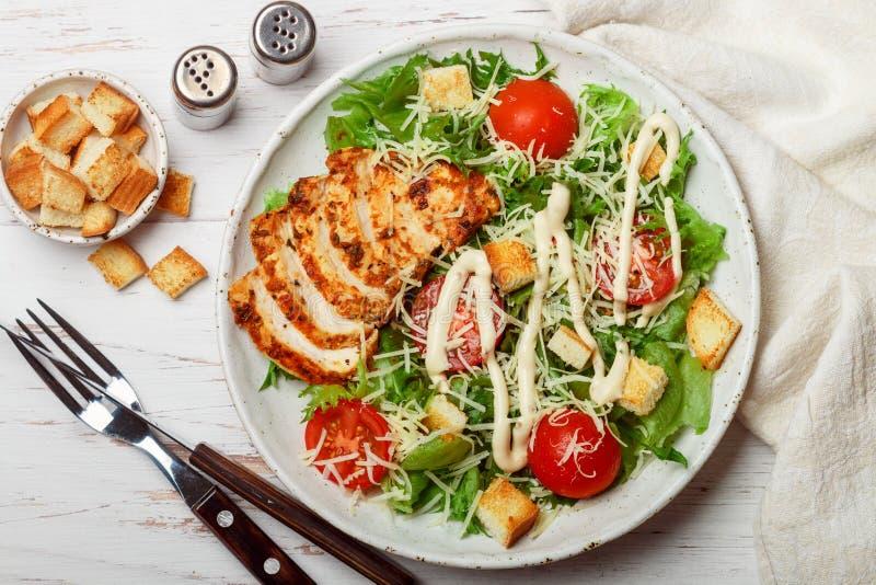 与冰山的健康烤鸡凯萨色拉或莴苣、乳酪巴马干酪、西红柿、面包油煎方型小面包片和食家调味汁 免版税库存图片