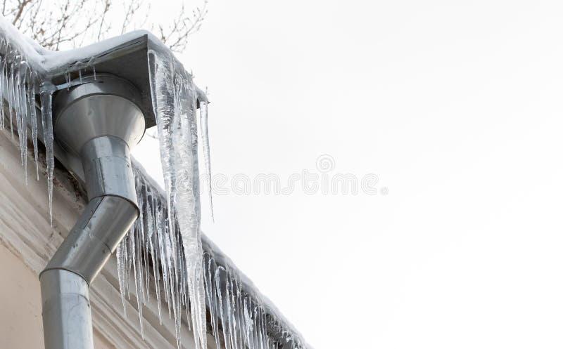 与冰柱的冰冷的落水管,在白色背景的年迈的屋顶 寒冷冬天天气概念 r 免版税库存图片
