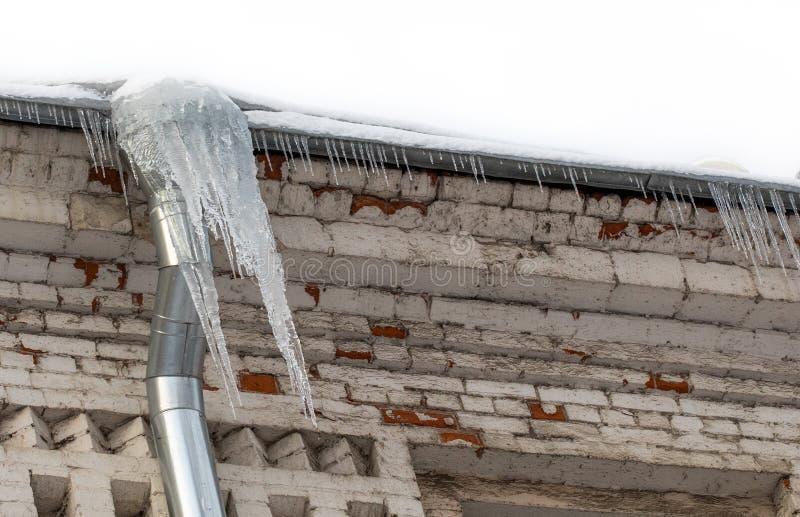 与冰柱的冰冷的落水管,年迈的屋顶框架 寒冷冬天天气概念 r 免版税库存图片