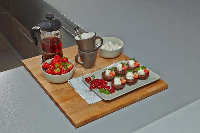 与冰淇凌、茶和草莓的供食的微型巧克力果仁巧克力 免版税库存照片