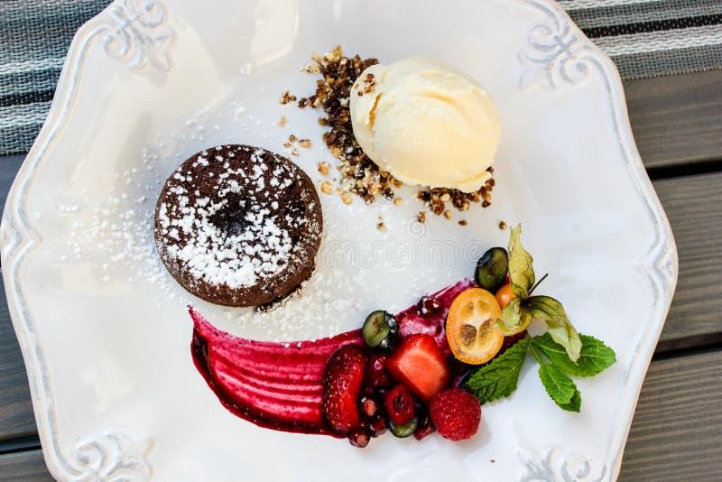 与冰淇淋和莓果的可口巧克力蛋糕在春天2019年 免版税库存图片