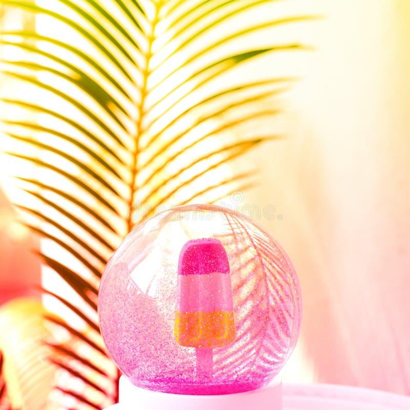 与冰淇淋的美丽的雪在棕榈树叶子背景里面的球和闪烁 免版税库存图片