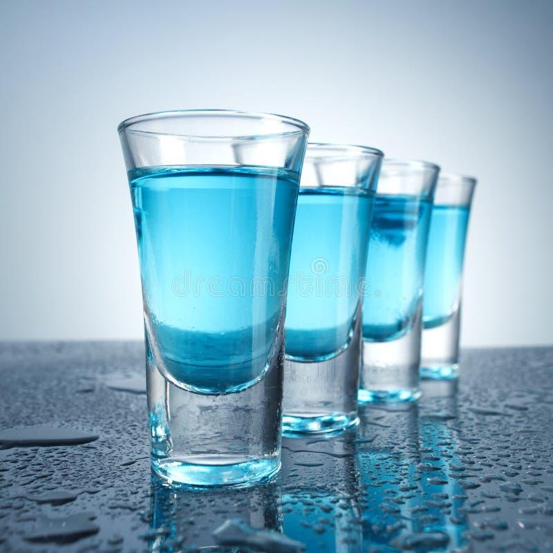 与冰的伏特加酒玻璃在蓝色背景 免版税图库摄影