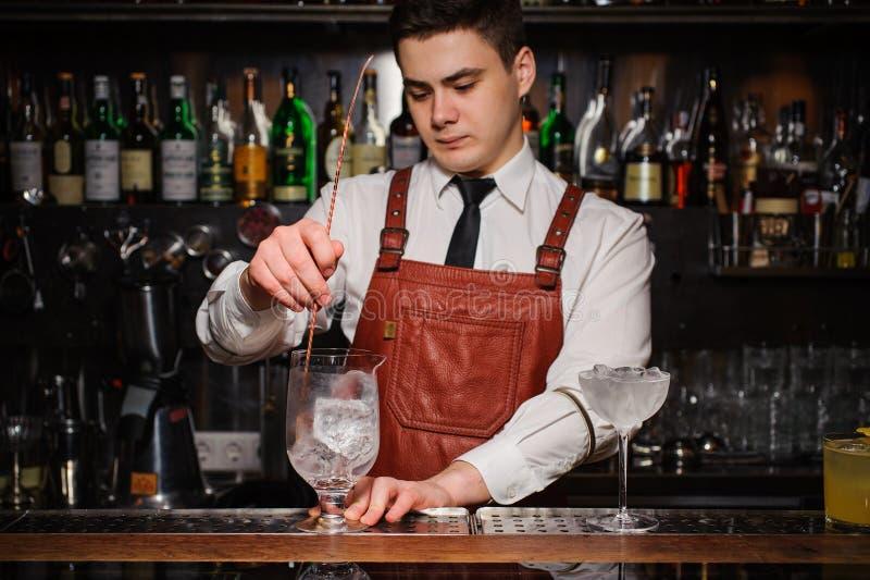 与冰的侍酒者冷却的鸡尾酒杯 免版税库存照片