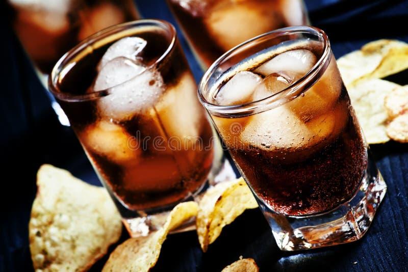 与冰的冷的可乐在玻璃和土豆片在一黑暗的backgro 库存照片