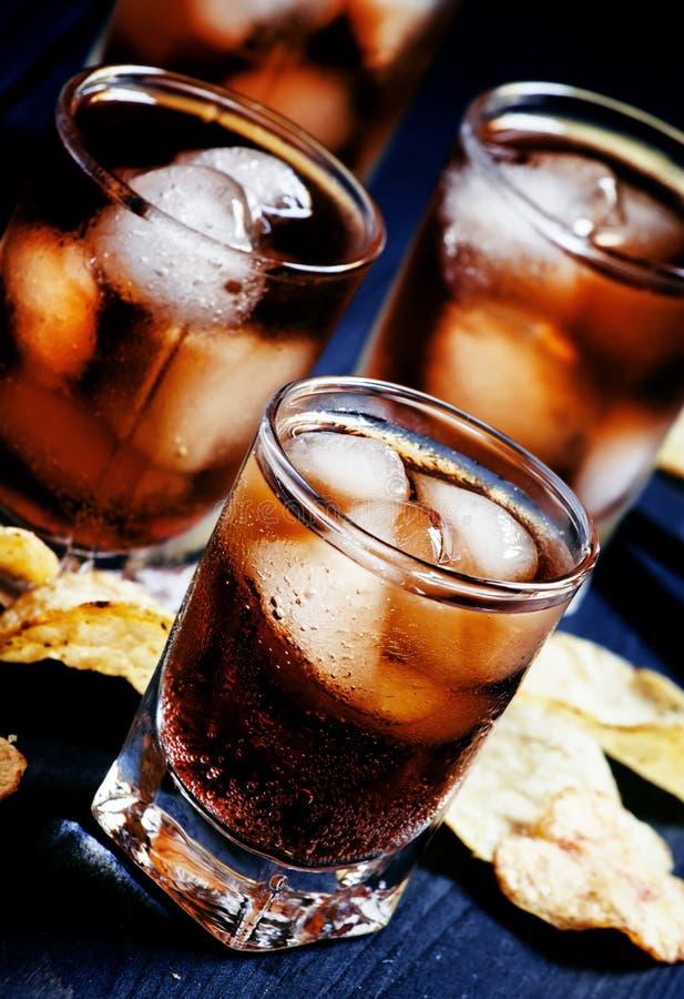 与冰的冷的可乐在玻璃和土豆片在一黑暗的backgro 免版税库存照片