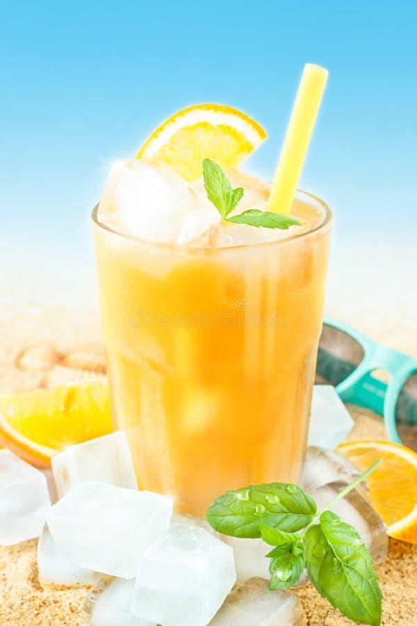 与冰的冷的橙汁在海滩背景 免版税图库摄影