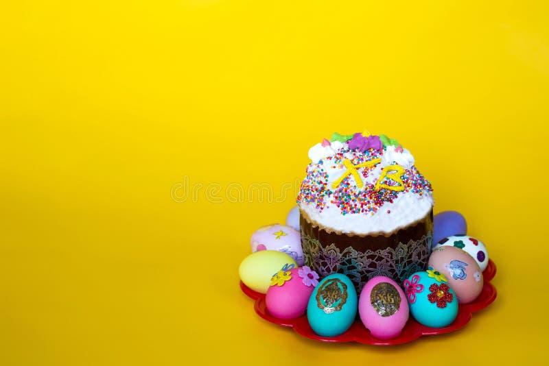 与冰的复活节蛋糕和在黄色背景的色的复活节彩蛋 免版税库存照片