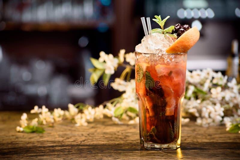 与冰的夏天鸡尾酒装饰用薄菏和莓果在一张木桌上在花卉背景 莓果mojito 免版税库存图片