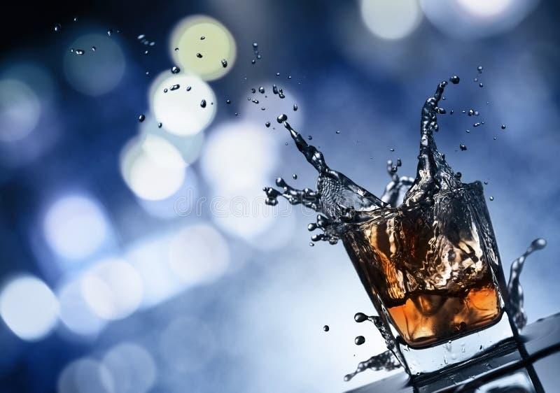 与冰的威士忌酒在夜城市背景  免版税库存照片