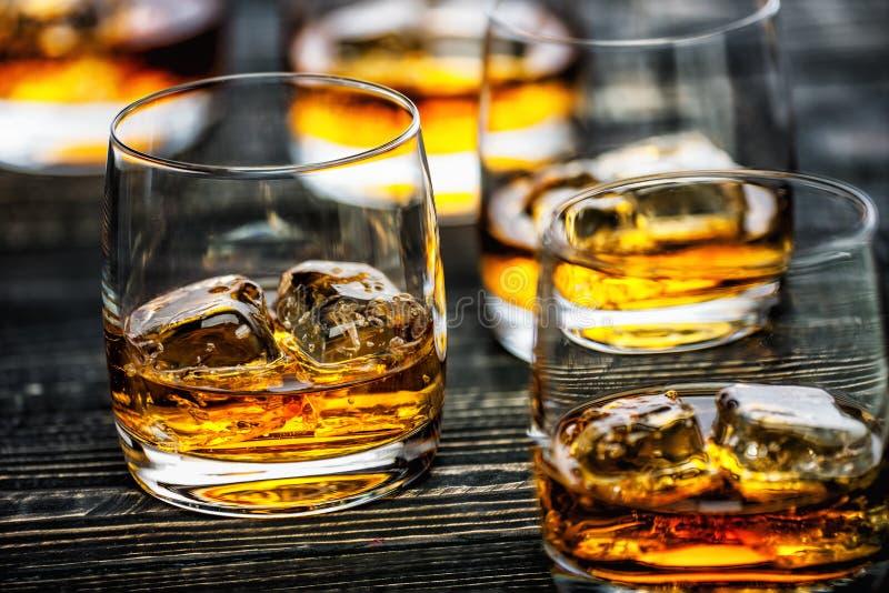 与冰的威士忌酒在黑木背景 库存照片