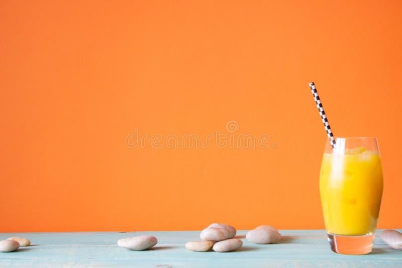 与冰的橙汁 橙色背景 背景概念框架沙子贝壳夏天 免版税库存图片