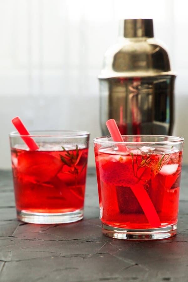 与冰的红色饮料 做酒吧工具、草莓和麝香草叶子的鸡尾酒 库存图片