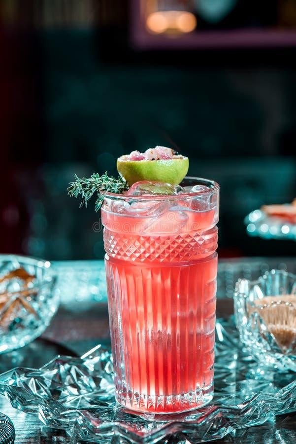 与冰的美丽的红色鸡尾酒在雕琢平面的玻璃,装饰用灼烧的石灰 在美好的水晶背景的鸡尾酒 免版税图库摄影