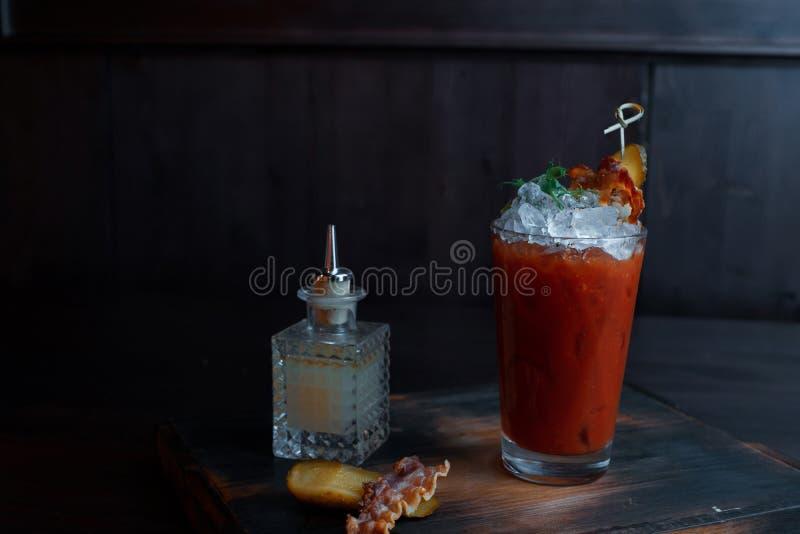 与冰的西红柿汁装饰用草本和烟肉片断  鸡尾酒在酒吧的一张老木桌上站立 库存照片