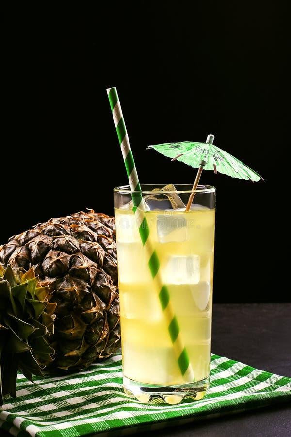 与冰管和伞的菠萝鸡尾酒在黑背景 热带水果,在一个黑暗的样式的夏天心情 免版税库存图片