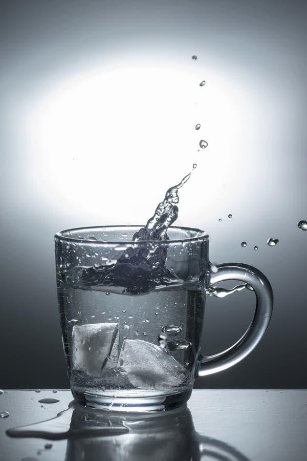 与冰落入水的,轻定调子的透明玻璃 免版税库存图片