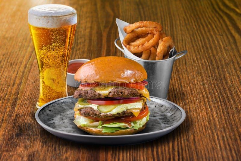 与冰镇啤酒和葱ringsFresh的新鲜的供食的牛肉汉堡供食了牛肉汉堡用冰镇啤酒和洋葱圈 免版税库存照片
