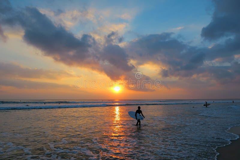 与冲浪板的年轻冲浪者剪影在美好的日落背景,库塔海滩,巴厘岛,印度尼西亚 免版税库存图片