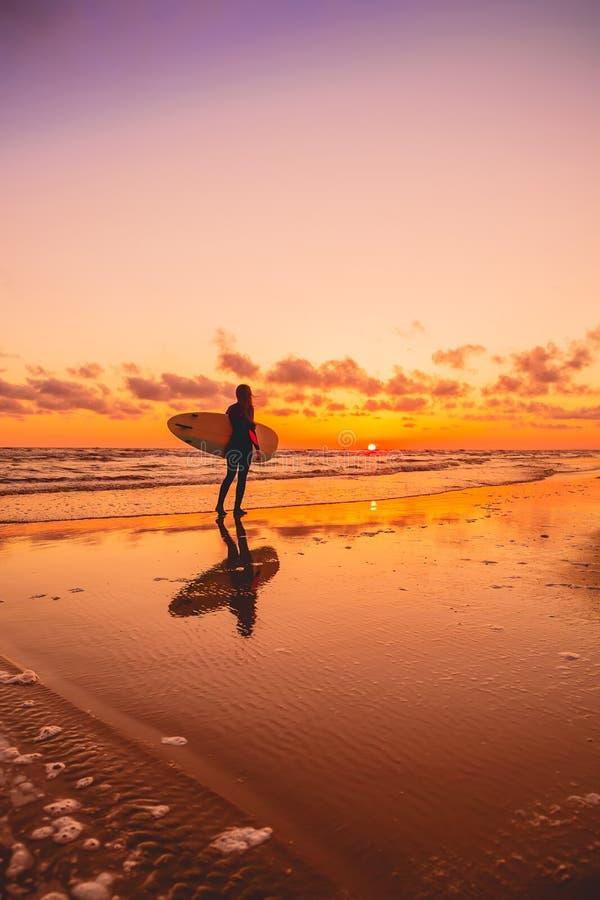 与冲浪者女孩和冲浪板的剪影在温暖的日落或日出的一个海滩 冲浪者和海洋 库存照片
