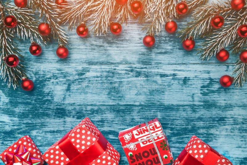 与冷杉分支、xmas球和礼物盒的圣诞节框架有在青海洋背景的红色丝带的 免版税库存图片