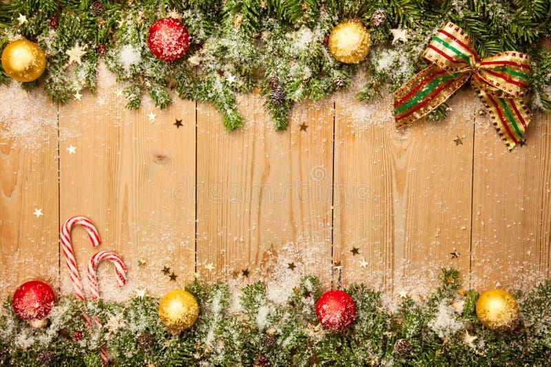 与冷杉木、糖果和中看不中用的物品的圣诞节背景与雪 图库摄影