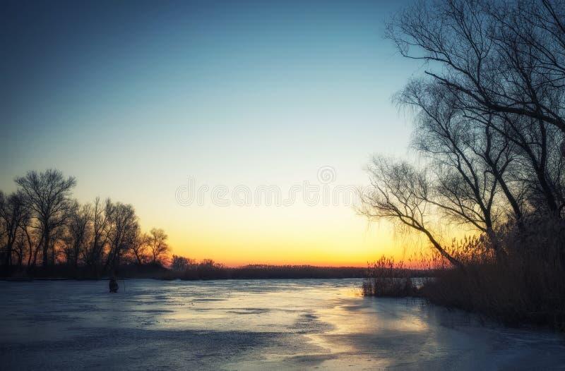 与冻河,树,渔夫的冬天风景 库存照片
