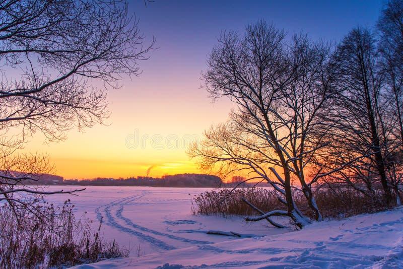 与冻湖和日落天空的五颜六色的冬天日落 免版税库存照片