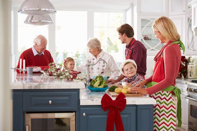 与准备圣诞节膳食的祖父母的家庭在厨房里 图库摄影