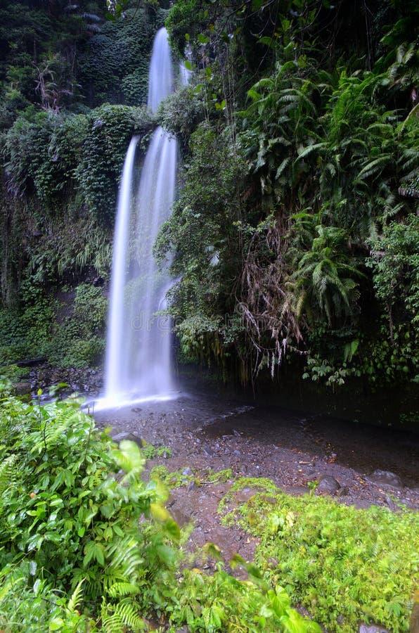 与凉快的空气和绿色风景的层状水流量是吸引力您能享用,当您参观Sendeng Gile瀑布时 免版税库存图片