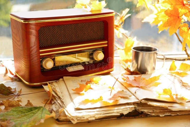 与减速火箭的收音机的老开放书和在窗台的秋叶 库存图片
