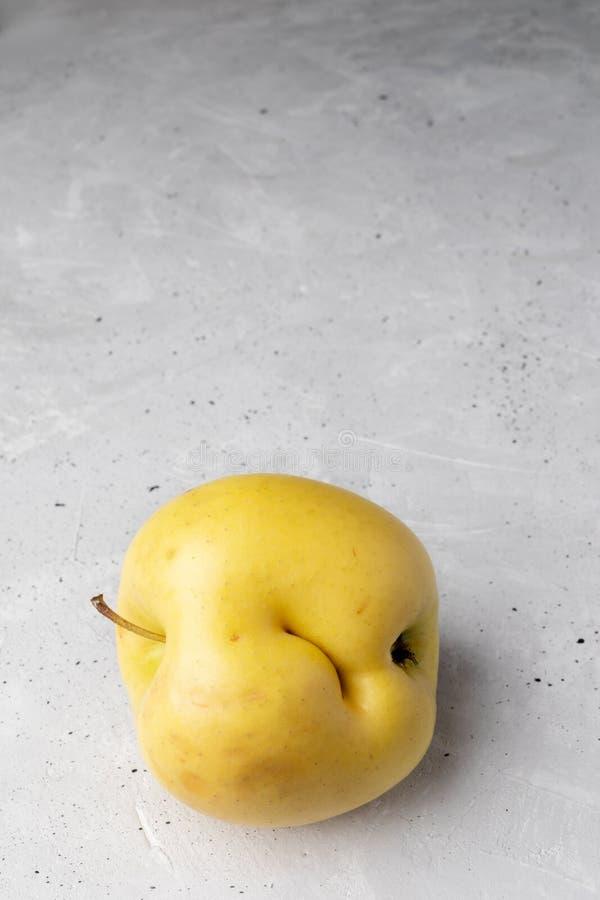 与凹痕的唯一丑恶的黄色苹果在具体背景 库存照片