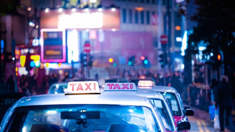 与出租汽车汽车的香港都市风景在夜城市街道 免版税图库摄影
