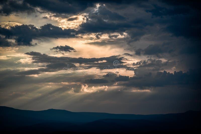与击穿他们的太阳的美丽的云彩在日落期间 库存照片