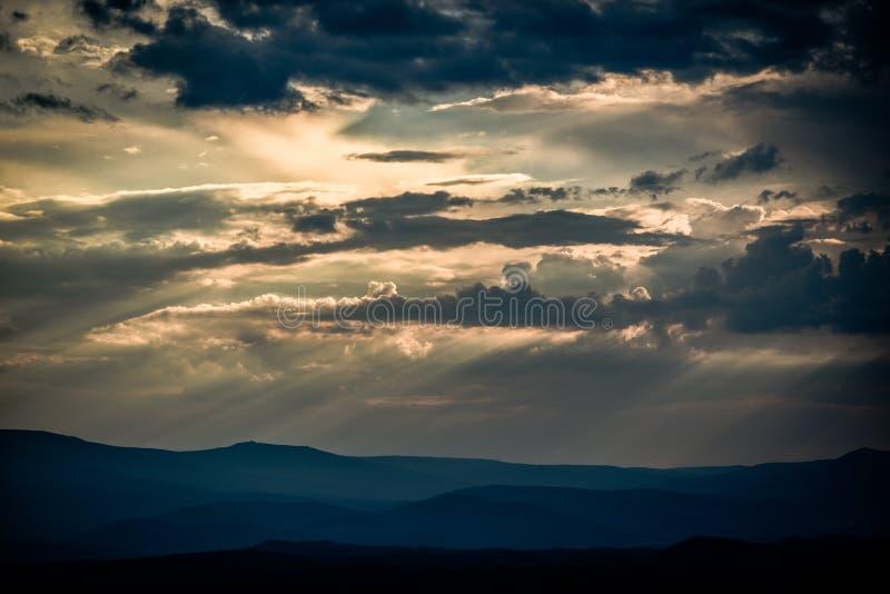 与击穿他们的太阳的美丽的云彩在日落期间 免版税库存图片