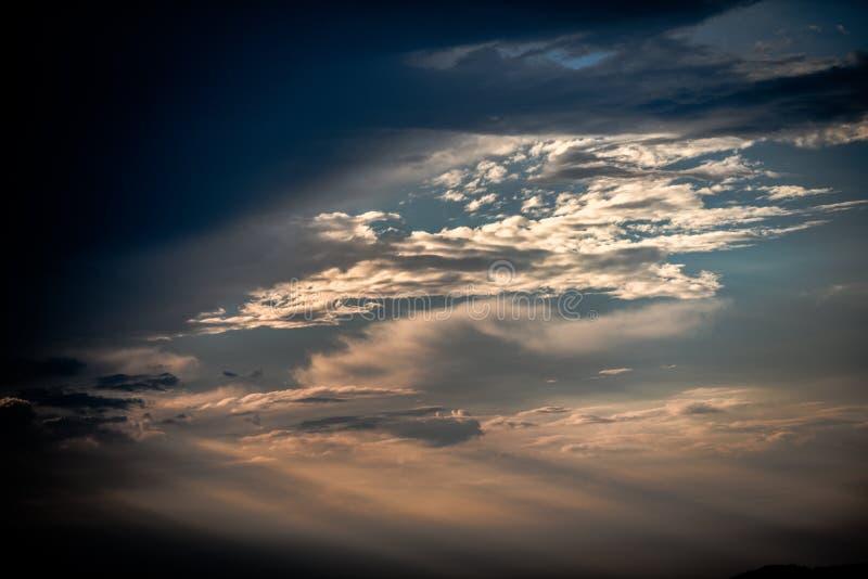 与击穿他们的太阳的美丽的云彩在日落期间 库存图片