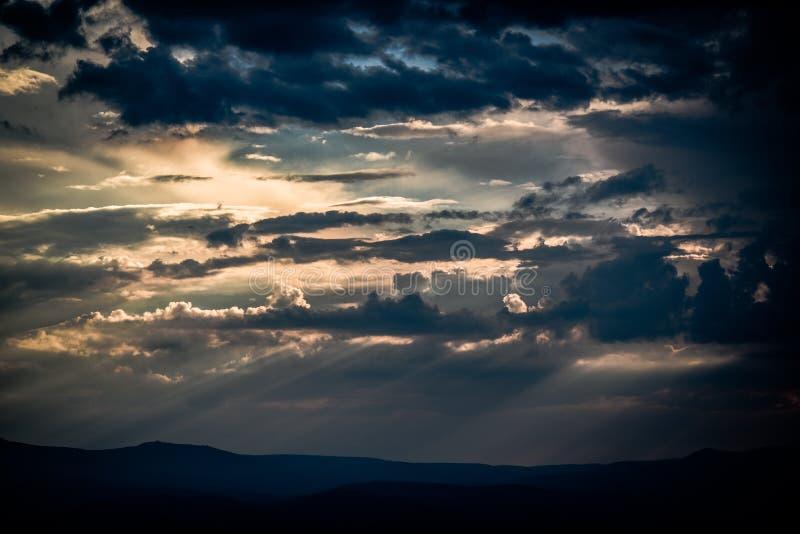 与击穿他们的太阳的美丽的云彩在日落期间 图库摄影
